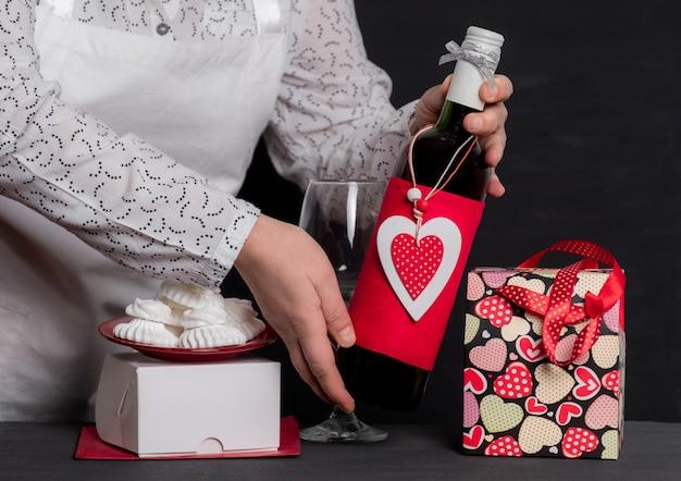 Livrer tenant une bouteille de vin avec coeur rouge de la saint-valentin près de sac de fête et boîte blanche pour gâteaux