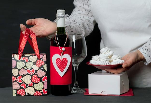 Livrer tenir des gâteaux près d'une bouteille de vin avec un cœur rouge de la saint-valentin et un sac de fête