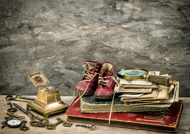 Livres anciens et photos, accessoires d'écriture et vieilles chaussures de bébé. image tonique de style vintage