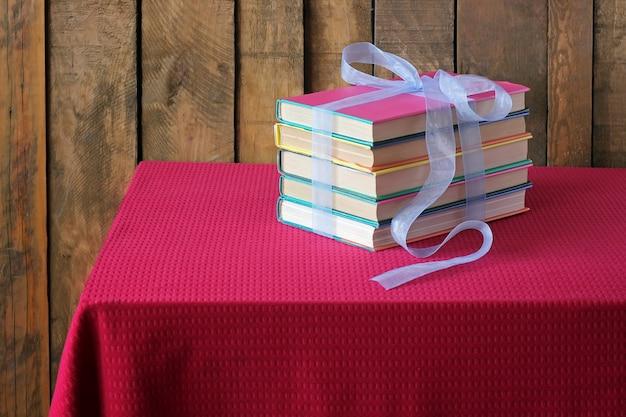 Les livres attachés par un ruban bleu sont posés sur une table avec un chiffon rouge.