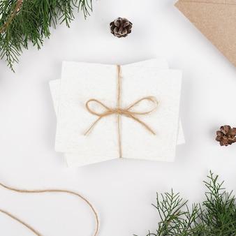 Livres blancs avec enveloppe artisanale avec des branches de sapin