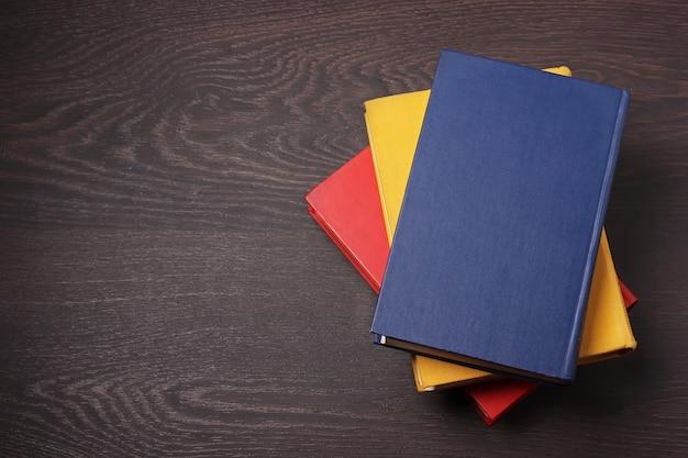 Livres bleus, jaunes et rouges sur une table en bois sombre, la vue de dessus.