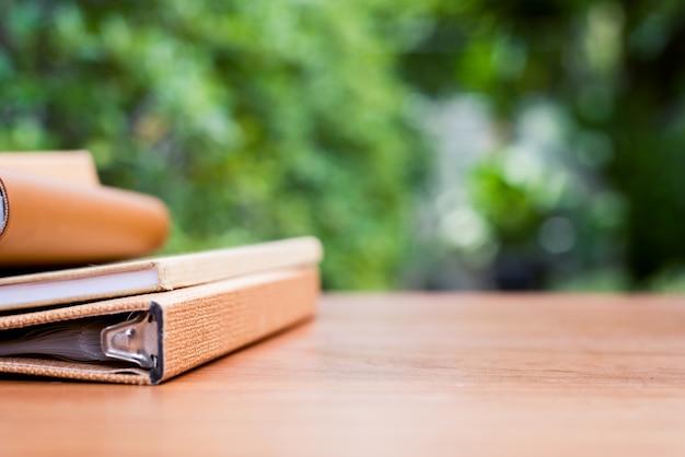 Des livres sur un bureau en bois à l'avant de la maison avec une vue floue sur le jardin.