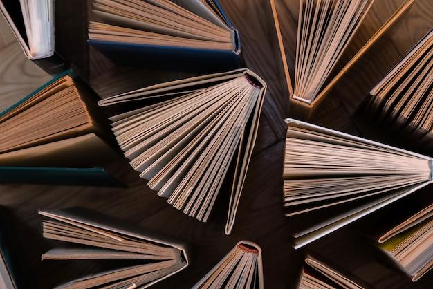 Livres cartonnés anciens et utilisés, manuels vus d'en haut sur un plancher en bois.