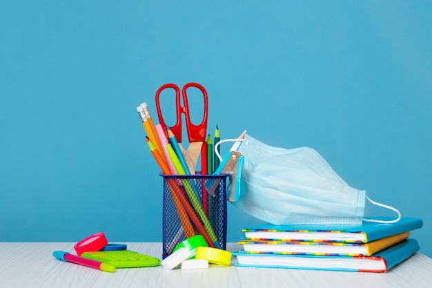 Livres colorés lumineux, réveil et crayons de couleur sur fond clair. retour à l'école.