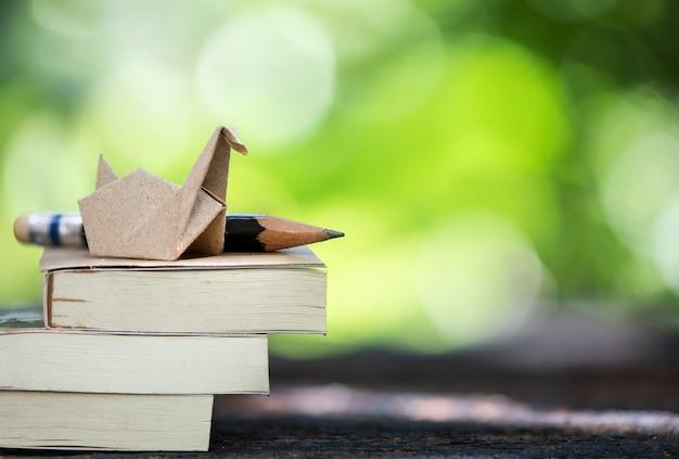Livres, crayon de bois et canard en papier dans la nature.