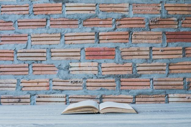 Livres sur une échelle en bois sur fond de mur de couleur
