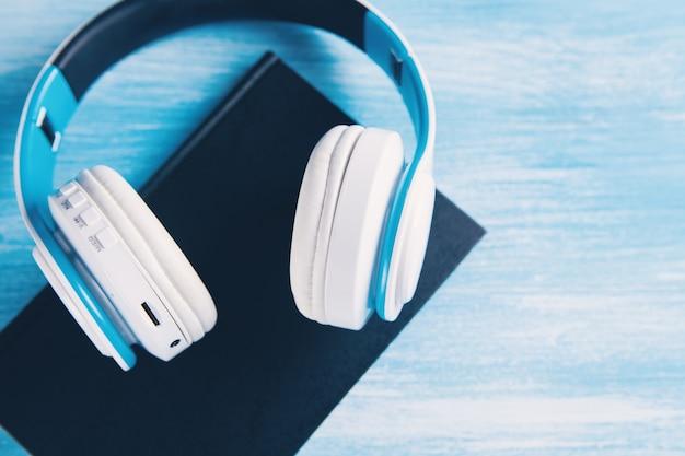 Livres et écouteurs modernes sur bleu clair