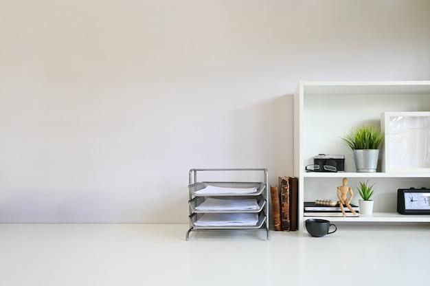 Livres sur l'espace de travail et papier avec appareil photo et fournitures de bureau sur les étagères.