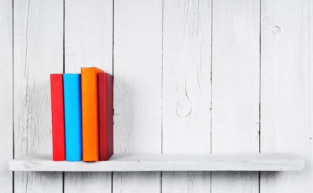 Livres sur une étagère en bois. sur un fond blanc en bois.