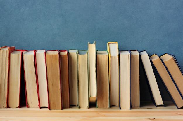 Livres sur l'étagère en bois sur un fond bleu.