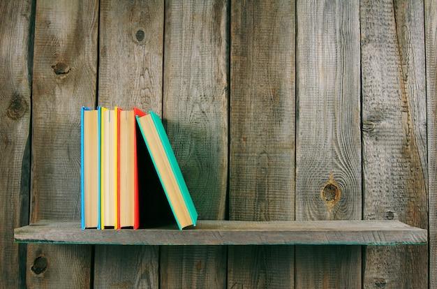Livres sur étagère en bois sur table en bois.