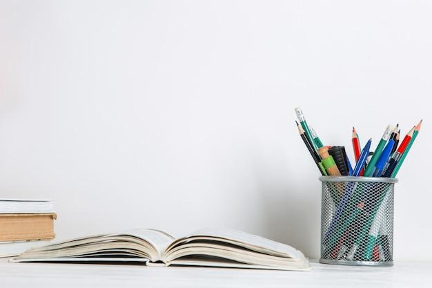 Livres et fournitures scolaires sur blanc.