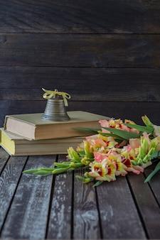 Livres, glaïeul et une vieille cloche
