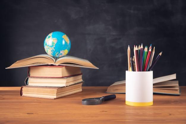 Livres, globe, crayons et loupe sur le fond du tableau noir