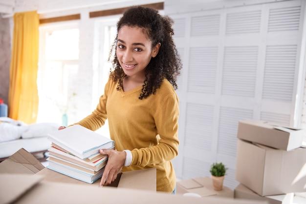 Livres importants. optimiste jeune fille posant pour la caméra et souriant tout en emballant des livres dans une boîte avant de quitter l'ancien appartement