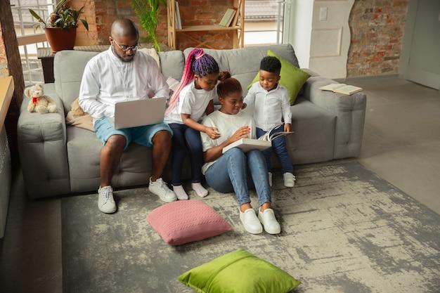 Livres lisant une famille africaine jeune et gaie pendant l'isolement de la quarantaine