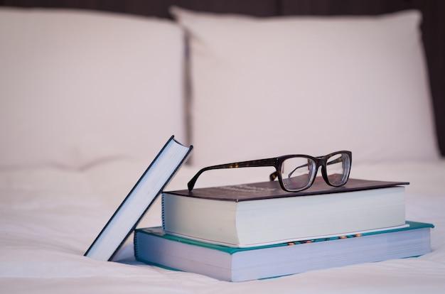 Des livres sur le lit blanc, des verres sur le dessus.