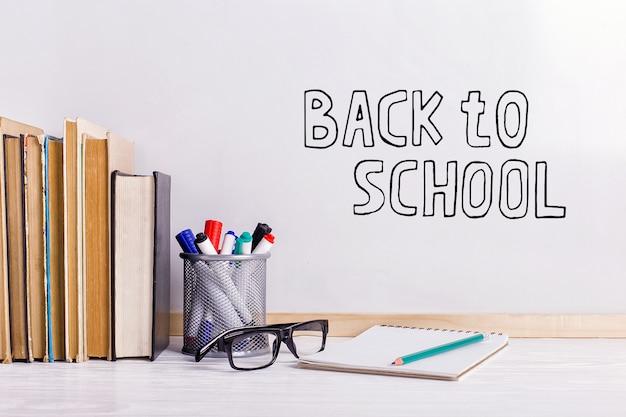 Livres, marqueurs, cahier, crayon et lunettes sur la table