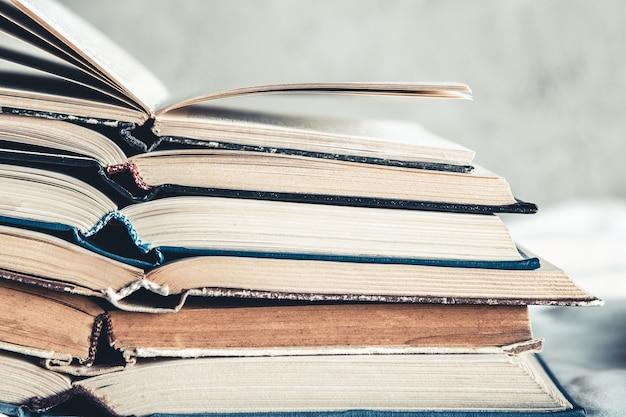 Livres ouverts dans une pile sur un fond clair. éducation, loisirs