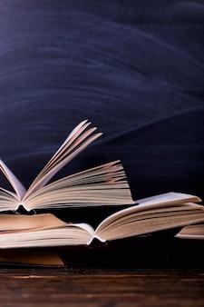 Les livres ouverts sont une pile sur le bureau, sur le fond d'un tableau noir.