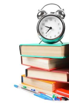 Des livres, un réveil et des outils scolaires. sur fond blanc.