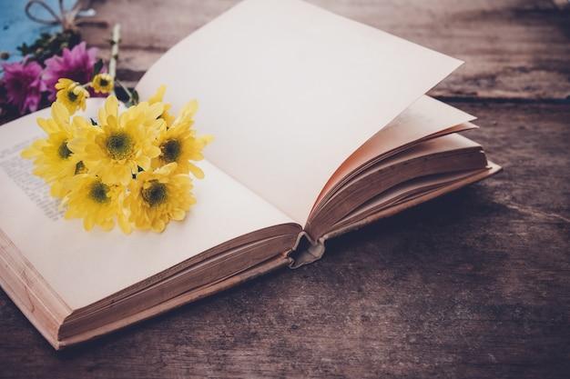 Livres romantiques avec bouquet de fleurs sur fond de bois ancien - concept de nostalgique et souvenir au printemps fond vintage