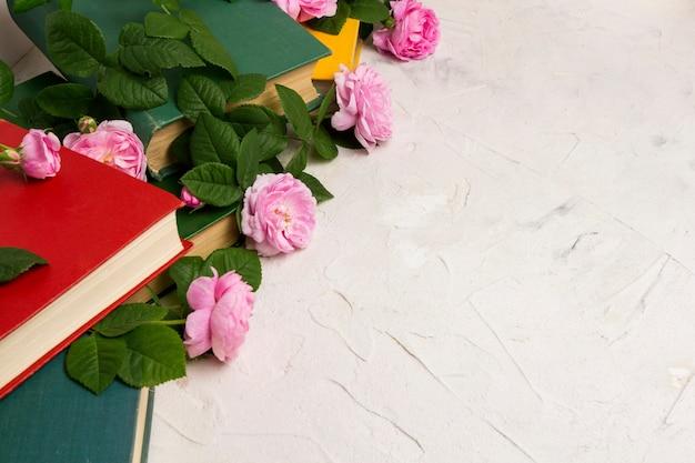 Livres et roses sur une surface de pierre claire. livres conceptuels sur l'amour et les romans romantiques