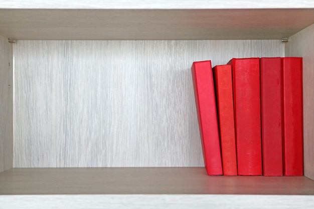 Livres rouges dans une étagère en bois.