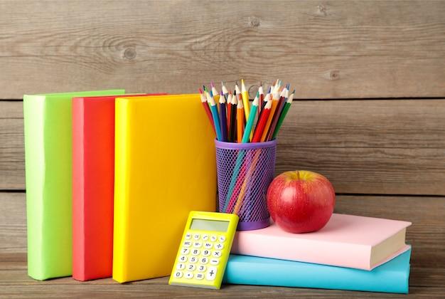Livres scolaires multicolores et papeterie sur fond de bois gris