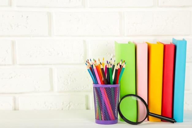 Livres scolaires multicolores et papeterie sur fond de mur de briques blanches