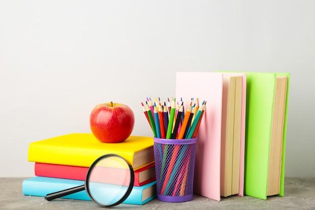 Livres scolaires multicolores et papeterie sur gris