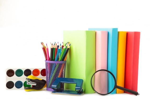 Livres scolaires multicolores et papeterie isolé sur blanc