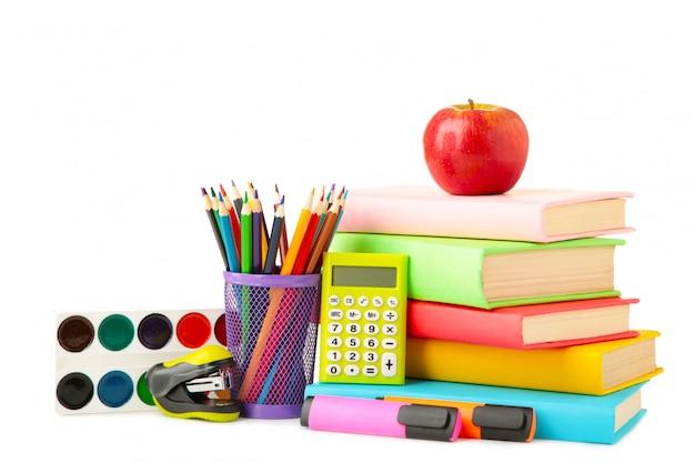 Livres scolaires multicolores et papeterie isolé sur mur blanc