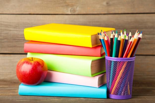 Livres scolaires multicolores et papeterie sur mur en bois gris