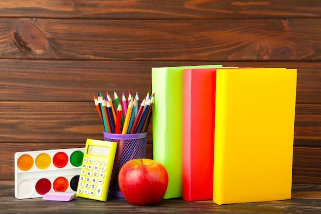 Livres scolaires multicolores et papeterie sur mur en bois marron