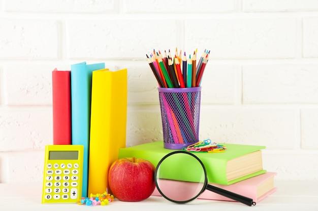 Livres scolaires multicolores et papeterie sur mur de briques blanches.