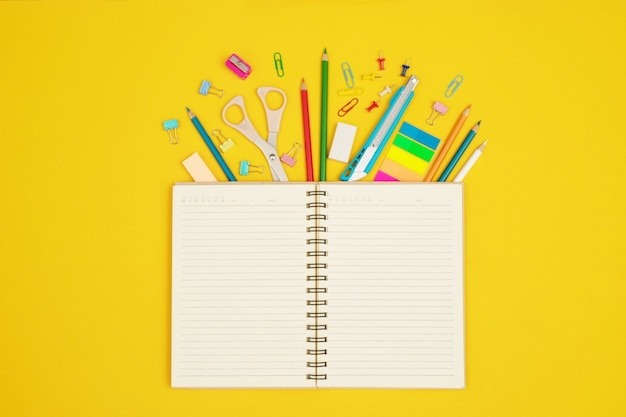 Livres superposés avec divers périphériques couleur utilisés dans le travail de document. décorez-les pour qu'elles soient belles et modernes sur un fond jaune.