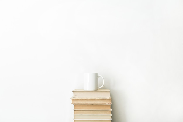 Livres et tasse de café sur une surface blanche
