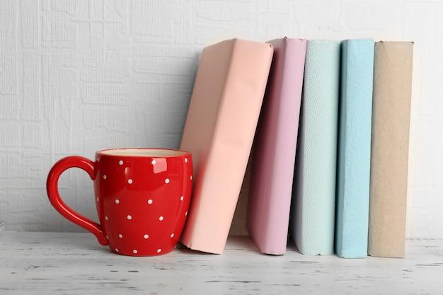 Livres et tasse sur étagère en bois
