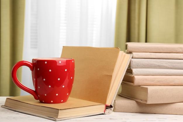 Livres et tasse sur table en bois, sur rideaux