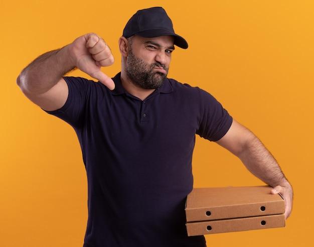 Livreur d'âge moyen mécontent en uniforme et casquette tenant des boîtes à pizza montrant le pouce vers le bas isolé sur un mur jaune