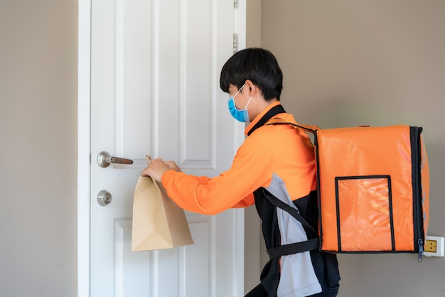 Un livreur asiatique envoie un sac de nourriture au bouton de la porte sans contact ou sans contact avec le livreur devant la maison pour une distanciation sociale en cas de risque d'infection concept de coronavirus