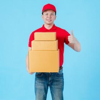 Livreur asiatique heureux portant une chemise rouge et un chapeau montrant les pouces vers le haut et portant des boîtes de colis en papier isolées sur fond de couleur bleue. concept de service de livraison postale.