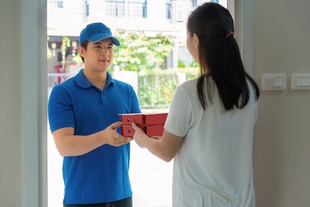Livreur asiatique jeune homme en uniforme bleu sourire et tenant des boîtes à pizza devant la maison