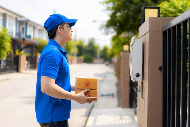 Livreur asiatique jeune homme en uniforme bleu sourire et tenant des tas de boîtes en carton dans le village de maison avant avec copie espace.