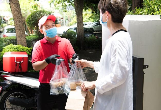 Livreur asiatique portant un masque facial et des gants en uniforme rouge livrant un sac de nourriture et de boisson au destinataire pendant l'épidémie de covid-19