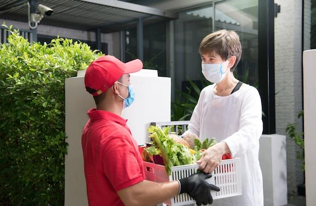 Livreur asiatique portant un masque et des gants en uniforme rouge livrant une boîte d'épicerie