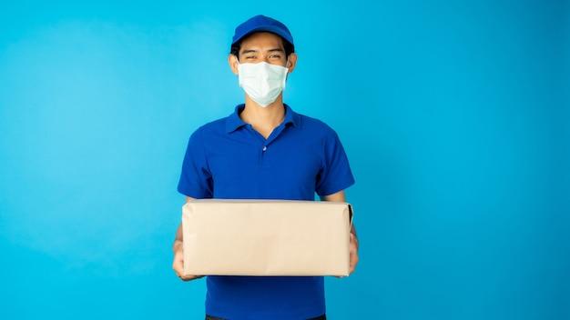 Livreur asiatique portant un masque et tenant une boîte à colis