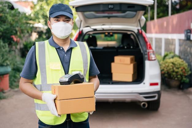 Livreur asiatique tenant des boîtes portant des masques pour empêcher la propagation du coronavirus ou du covid-19